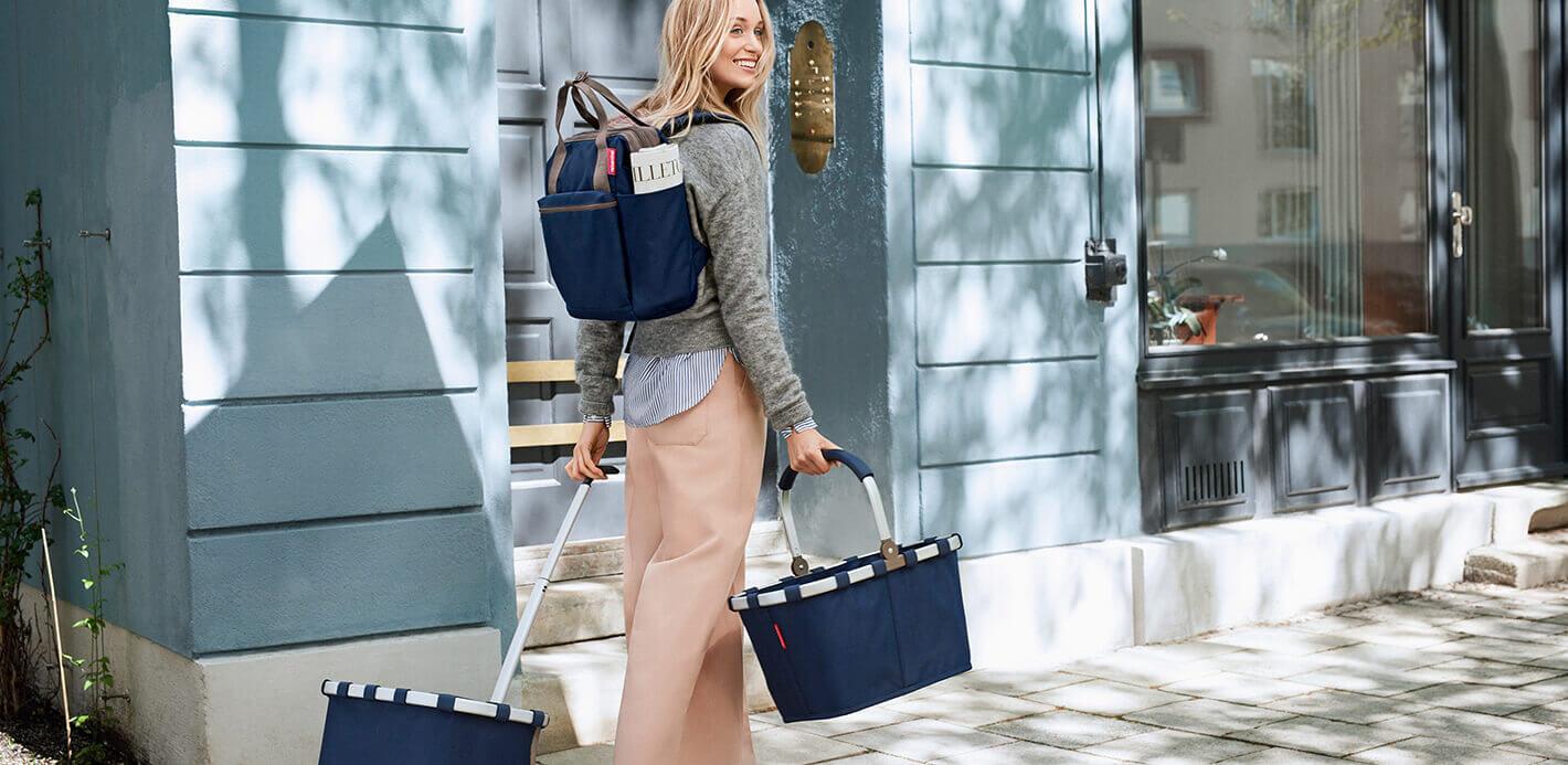 Frau mit Einkaufstasche und -trolley von Reisenthel.
