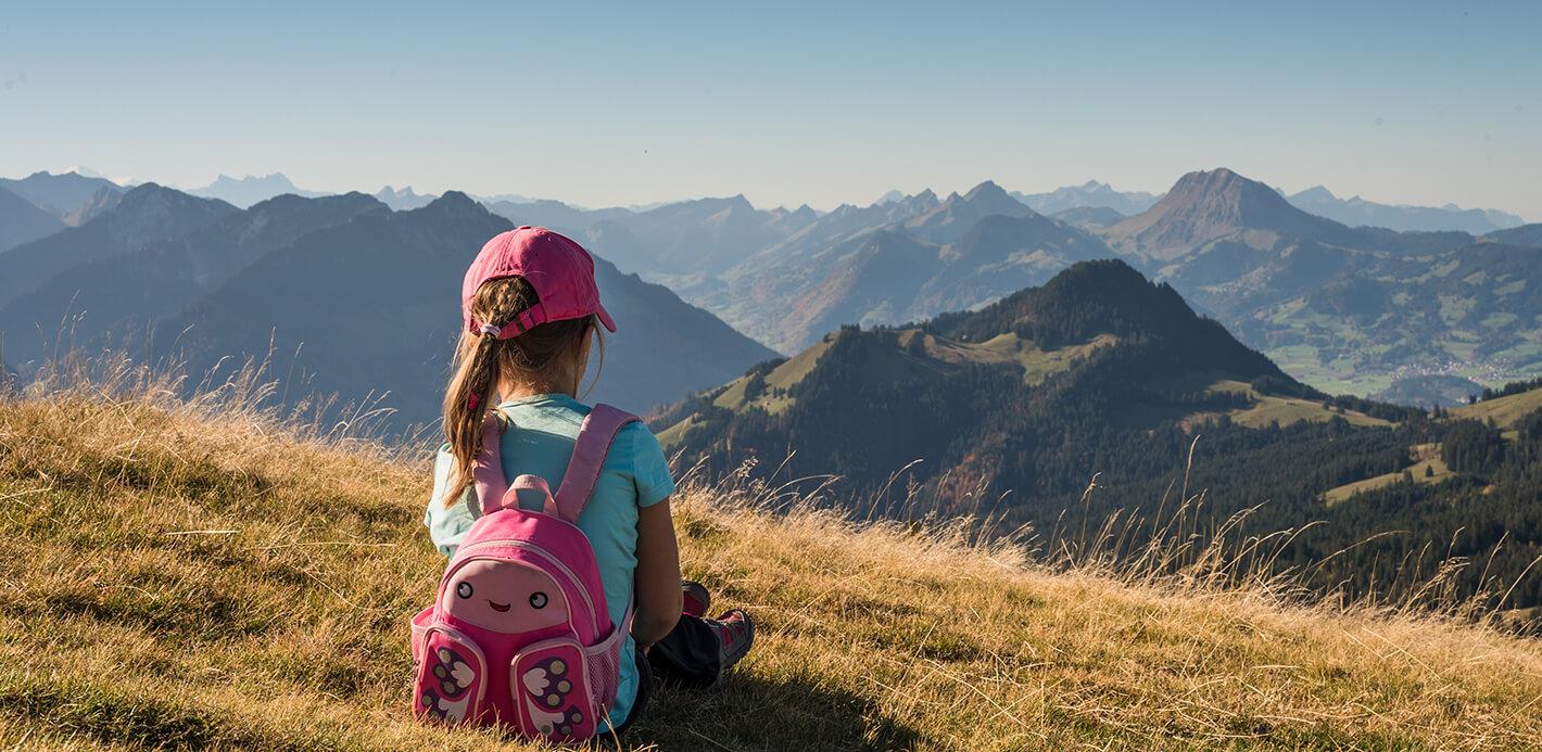 Kind mit Rucksack sitzt in den Bergen auf einer Wiese